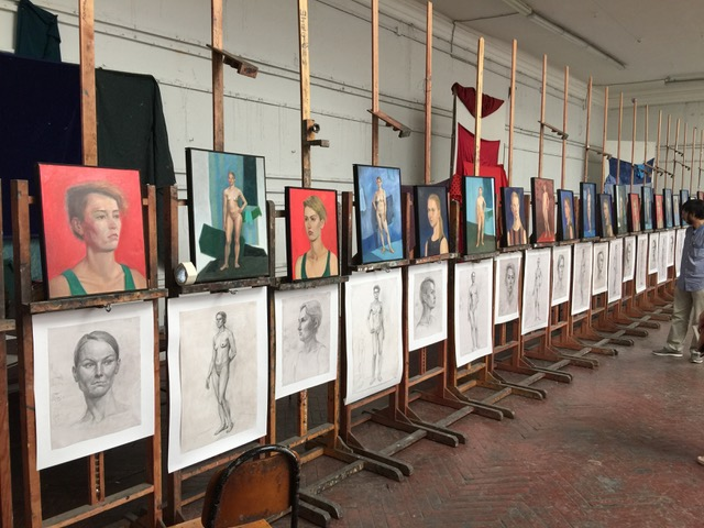 A photo of many graphite and oil painting figure studies lined up on easels.