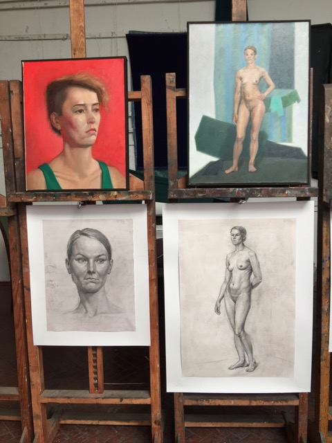 Two easels each prepared with two figure studies, one in oil paint and the other in graphite.